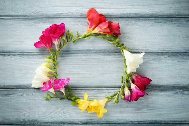木製の背景に美しいフリージアの花で作られたフレーム