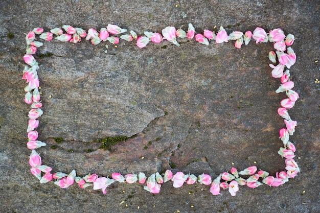 岩が多い背景に花で作られたフレーム。
