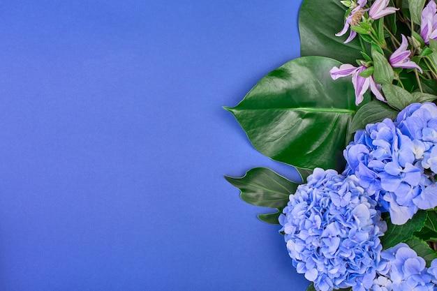青い空間に青いアジサイと緑の葉で作られたフレーム。フラット横たわっていた、トップビュー。ウェディングスペース