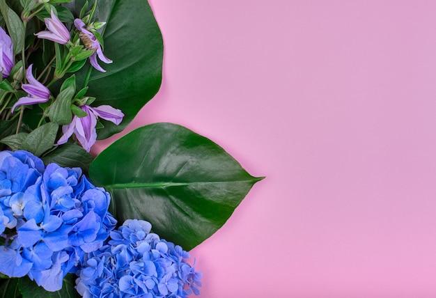 青いアジサイとバラの背景に緑の葉で作られたフレーム。フラット横たわっていた、トップビュー。結婚式の背景