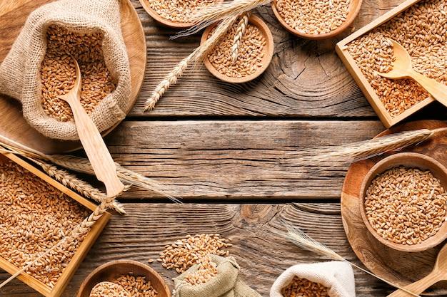 나무 배경에 밀 곡물 그릇과 가방으로 만든 프레임