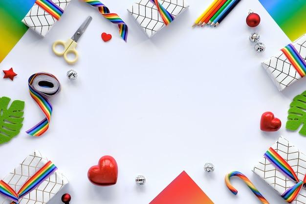 Lgbtqコミュニティの旗の色のレインボーリボンとクリスマスプレゼントで作られたフレーム。