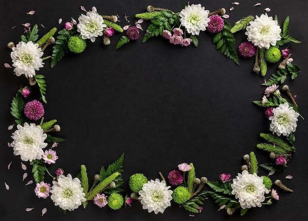 黒の背景に分離された色とりどりの花菊で作られたフレーム。花の構成。菊の花の夏の花輪。フラットレイ。