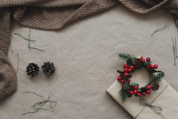 クラフト紙の背景にモミと松の木の枝と円錐形で作られたフレーム