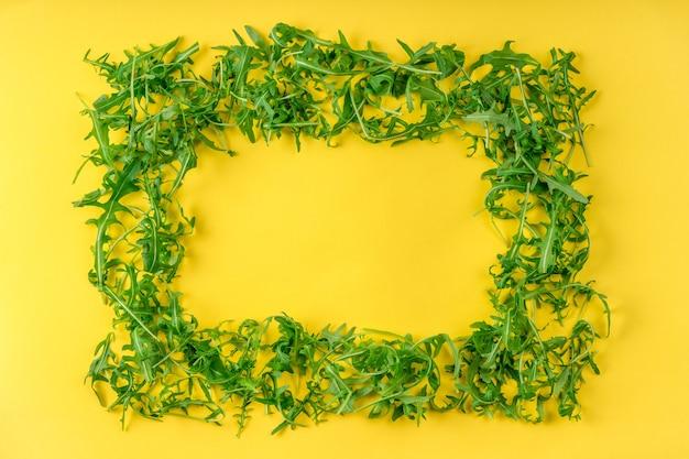 黄色い表面に新鮮なルッコラの葉で作られたフレーム。野菜サラダの材料。健康的な食事、創造的な食品のコンセプト。