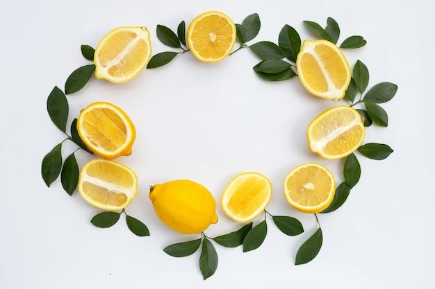 Рама из свежего лимона с зелеными листьями на белом фоне.