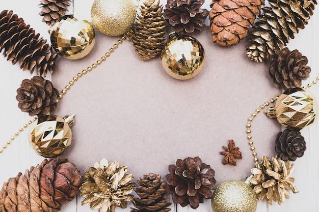 金色のクリスマスボール杉と松ぼっくりで作られたフレーム