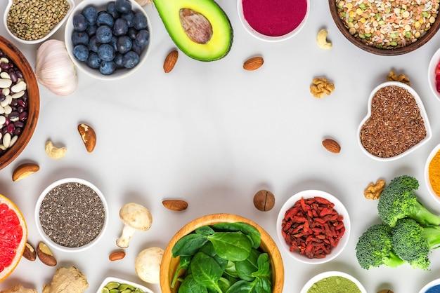健康的なビーガンフードのきれいな食事の選択で作られたフレーム:果物、野菜、種子、スーパーフード、ナッツ、白い大理石の背景にベリー。コピースペースのある上面図