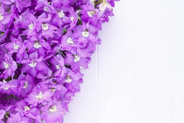 흰색 판자 배경에 라일락 델피니움 꽃으로 만든 프레임. 평면도. 공간을 복사합니다.