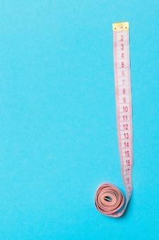 파란색 배경에 측정 테이프로 만든 프레임입니다. 재봉 개념의 상위 뷰입니다. 디자인을 위한 빈 공간이 있는 슬림한 허리 개념.