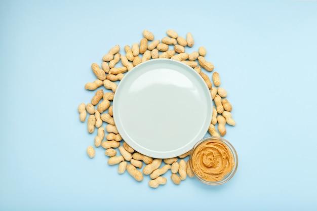 Рама из орехов арахиса в скорлупе с копией пространства в центре на синем фоне со сливочной арахисовой пастой в открытой стеклянной банке, арахисовым маслом. плоская планировка с местом для текста для арахисового масла.