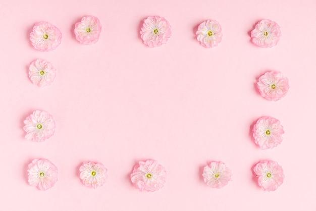 パステルピンクの背景にピンクの桜の花で作られたフレーム。フラットレイ。上面図。結婚式、バレンタインデー、女性の日のコンセプト