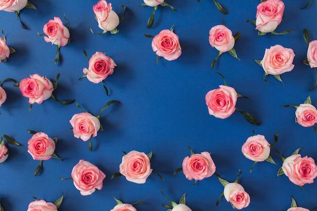 青い表面にピンクのバラの花のつぼみで作られたフレーム