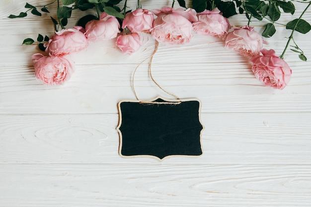 白い木製の背景にピンクのバラの花で作られたフレーム。