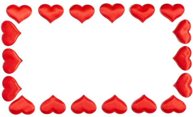 白い背景に分離された赤いハート、バレンタインデーのコンセプトで作られたフレーム。