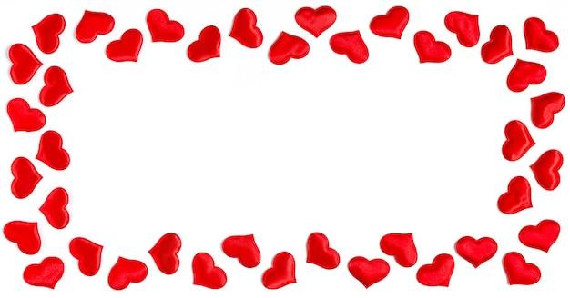 白い背景、バレンタインデーのコンセプトに分離された赤いハートで作られたフレーム。