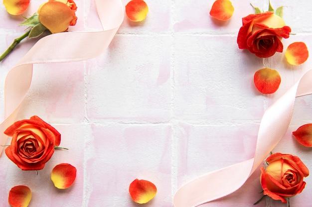Рамка из красных роз и лепестков с подарочной коробкой на мраморном фоне