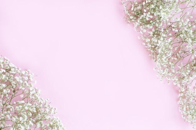 パステルピンクの背景に小さな白い花で作られたフレーム。カスミソウ。