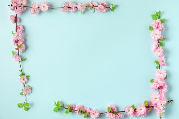 青い背景に春のピンクの桜の枝で作られたフレーム。フラットレイ。上面図。コピースペースのある休日や結婚式のレイアウト