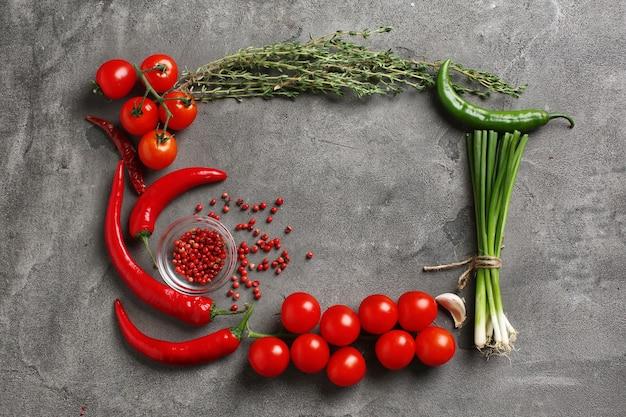 灰色の背景にトマト、スパイス、ハーブで作られたフレーム