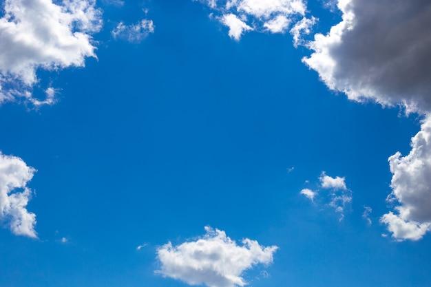 真っ青な空を背景に白い雲で作られたフレーム。テキスト用のスペース、コピースペース。
