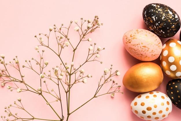 Рама изготовлена из деревянных крашеные яйца в золотой, черный и розовый цвета на розовом фоне. счастливой пасхи фон с копией пространства