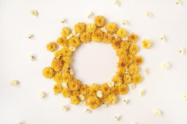 白い背景の上の黄色の野生の花のつぼみで作られたフレーム。フラットレイ、上面図