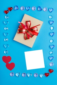 In a frame made of pebbles of hearts on a blue surface, a box with a bow