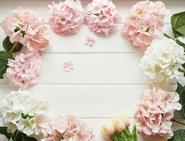 Frame made of pink and beige hydrangea flowers and yellow tulips