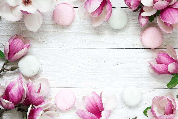 Frame made of pink magnolia flowers with macarons over white wooden table. mock up. flat lay. top view