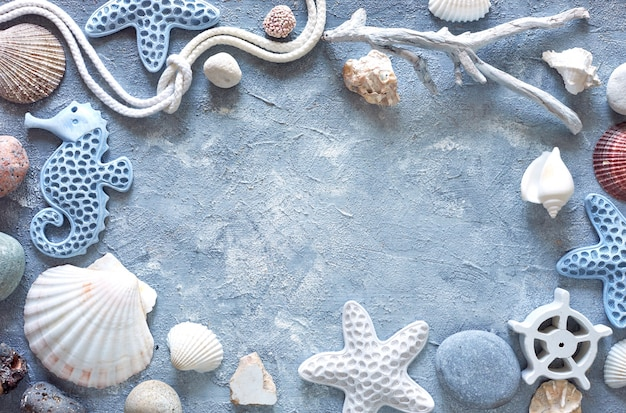 Frame made of sea shells, stones, rope and star fish on blue textured