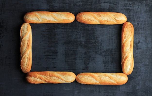 Frame made of six loafs of french baguette on black wooden background.