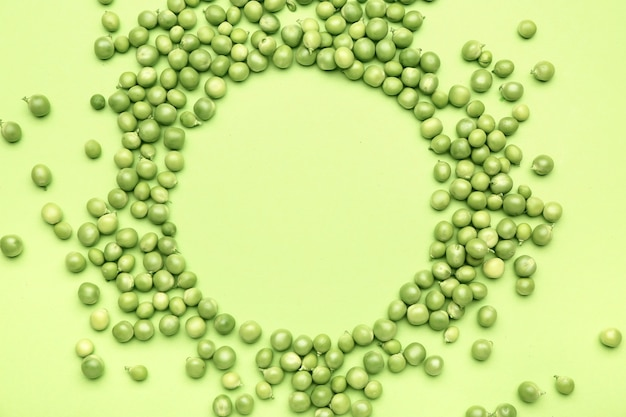 Frame made of tasty fresh peas on color background