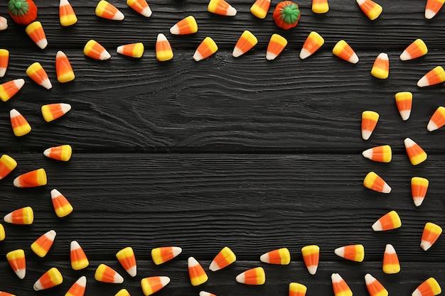 Frame made of tasty halloween candies on dark wooden background