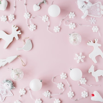 Frame made of white christmas decoration with christmas glass balls on pink background.