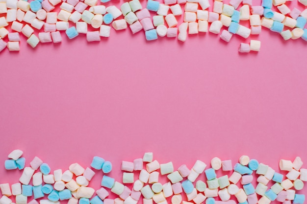 Frame made of white and pink sweet marshmallow candys with copy space on a pink background.