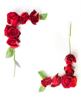Frame made with decorated red roses on white background