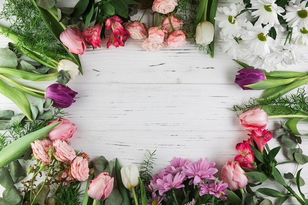 Frame made with different type of beautiful flowers on wooden surface