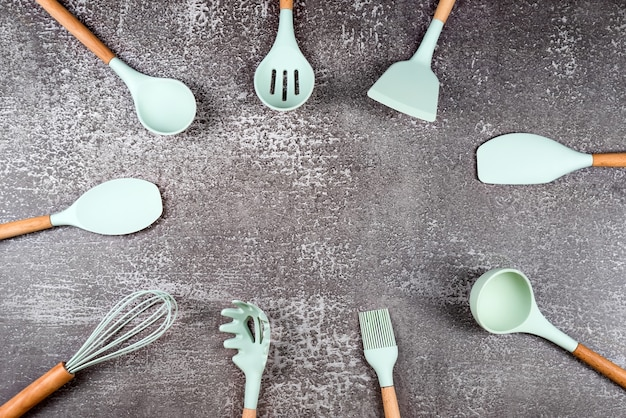 Frame made with kitchen utensils, home kitchen tools, mint rubber accessories on dark background. restaurant, cooking, culinary, kitchen theme. silicone spatulas and brushes, free space for text.