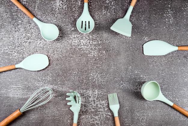 暗い背景に台所用品、家庭用キッチンツール、ミントラバーアクセサリーで作られたフレーム。レストラン、料理、料理、キッチンのテーマ。シリコンヘラとブラシ、テキスト用の空きスペース。