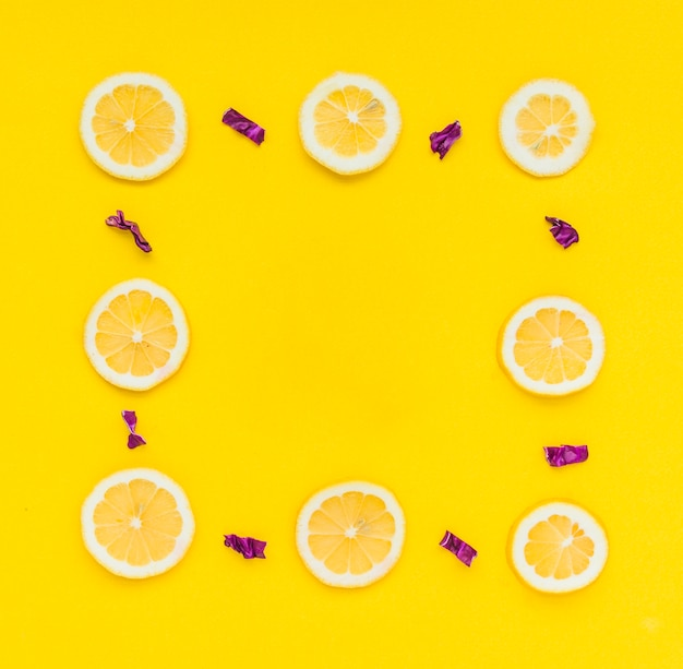 Frame made with sliced lemons and chopped purple cabbage on yellow background