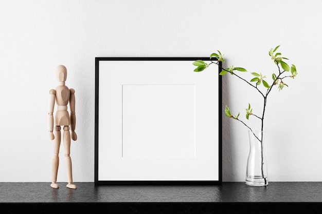 フレームモックアップ。花瓶と木製の人間の植物とポスター。パスパルトゥー付きの黒い四角いフォトフレーム。側面図。デザインやアートワークのテンプレートとして使用できます。
