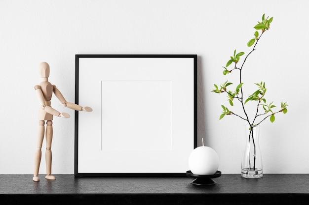 フレームモックアップ。花瓶、キャンドル、木製の人間の植物とポスター。パスパルトゥー付きの黒い四角いフォトフレーム。側面図。デザインやアートワークのテンプレートとして使用できます。