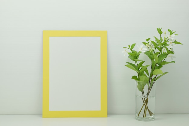 Frame mockup with flowers in a clear glass vase on white.