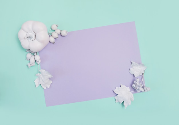 Frame mockup with pumpkin, berries and leaves on turquoise and violet card