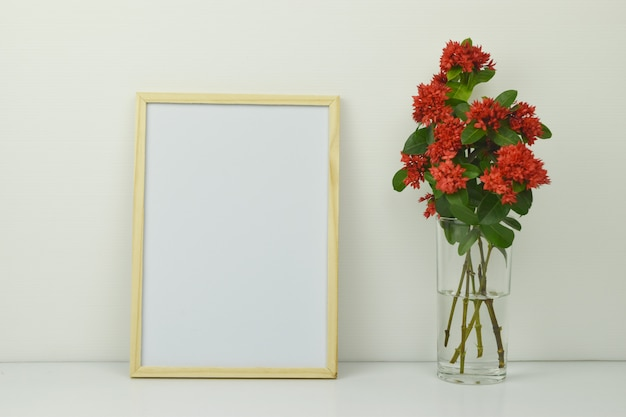 Frame mockup with red spike flowers in a clear glass vase on white .