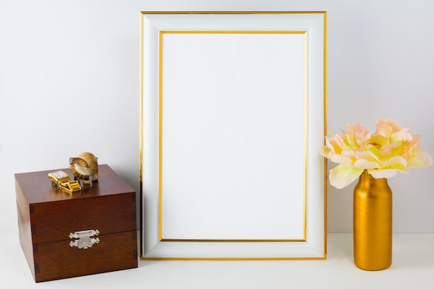 Frame mockup with wooden box and golden vase