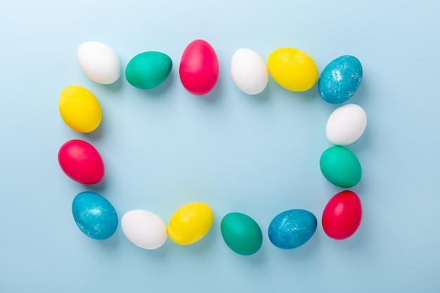Frame of multicolored easter eggs on blue background. easter composition. copy space. mockup