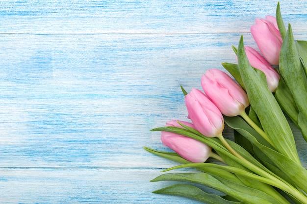 青い木の表面にピンクのチューリップの花の美しい花束のフレーム