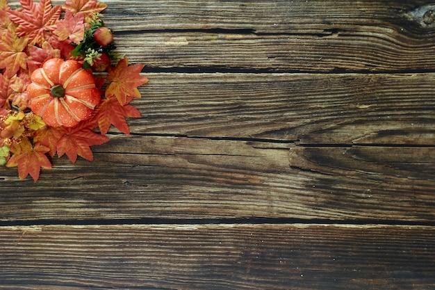 秋の葉とカボチャのフレームコピースペースと古い木製の背景